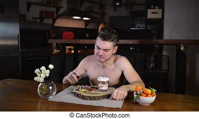 Young man sits at table and eats pancakes