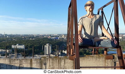 Young man sits in lotus asana on a metalic ladder of a building