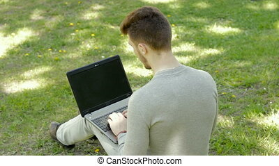 Young man sits on a grass in the park and taping on laptop computer