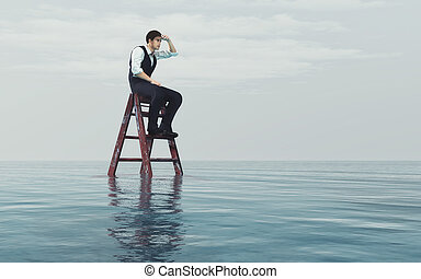 Young man sits on a ladder into the ocean and look at the...