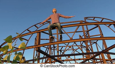 Young man sits on a metallic construction at sunset in slo-mo