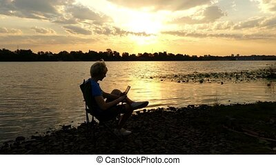 Young Man Sits on a Riverbank, Looks at a Tablet pc at a Sunset