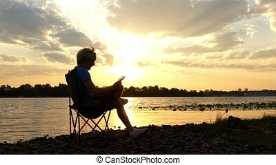 Young Man Sits on a Riverbank, Reads His Notes in the Rays of a Sunset in 4k
