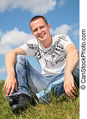 Young man sits on grass
