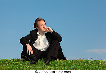 young man sits on meadow against sky