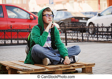 Young man sitting against a city traffic
