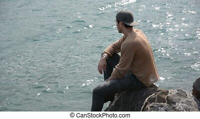 Young Man Sitting and Thinking in front of Sea