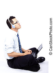 Young man sitting and using a laptop listen to the music