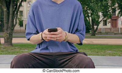 Young Man Sitting and Using a Phone in Town