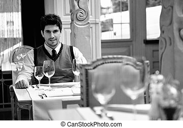 Young man sitting and waiting food at stylish restaurant