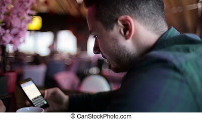 Young man sitting at a bar and sending message on the mobile phone