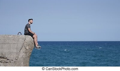 Young Man Sitting at Beach Boulders - Shirtless Young...