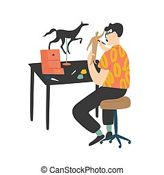 Young man sitting at desk and painting handcrafted miniature paper model figures isolated on white background. Male character enjoying his hobby at home. Flat cartoon colorful vector illustration.