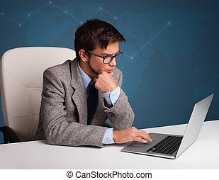 Young man sitting at desk and typing on laptop