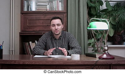 Young man sitting at desk with papers and talking about his report into the camera
