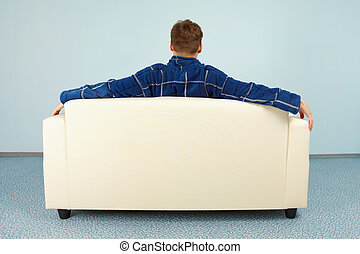 Young man sitting at home on couch