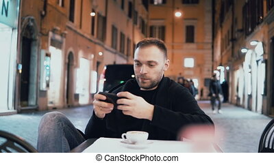 Young man sitting at the evening in the city cafe and holding smartphone. Attractive male drinking coffee alone.