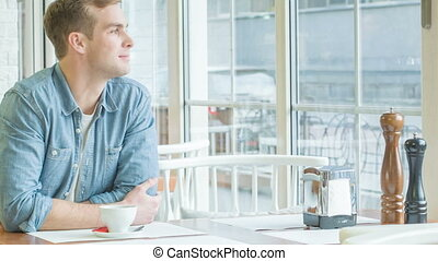 Young man sitting at the table and smiling. - Coffee time....