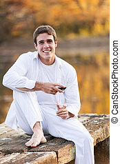 young man sitting by a lake with wine glass