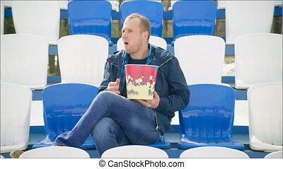Young man sitting cross-legged on the tribune