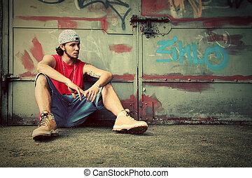 Young man sitting. Grunge graffiti wall - Young man sitting...