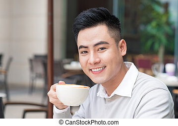 Young man sitting in a cafe on a coffee break.