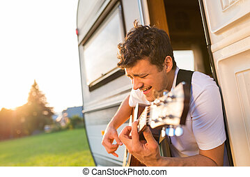 Young man sitting in a camper van - Handsome young man...