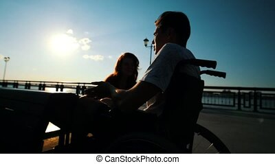 Young Man Sitting In A Wheelchair And Talking To A Girl...