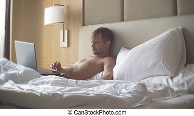 Young man sitting in bed with his laptop computer open and smartphone. He's working on it. 4k