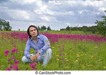 Young man sitting in green meadow