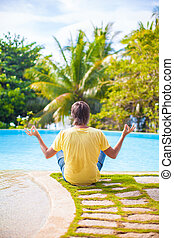 Young man sitting in lotus position near the pool