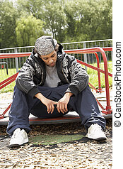 Young Man Sitting In Playground