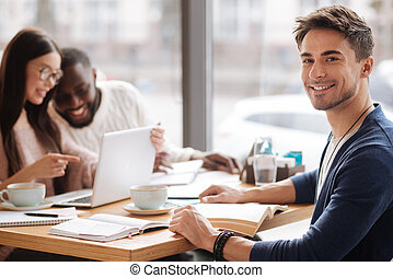 Young man sitting in the cafe - Studying together. Young...