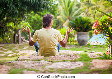 Young man sitting in the lotus position