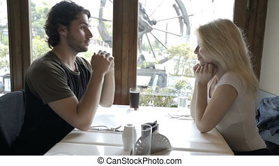 Young man sitting in the pub with his charming girlfriend at the table kissing her hand