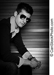 Young man sitting in the window with sunglasses in black and white