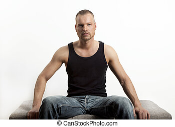 young man sitting, looking at the camera
