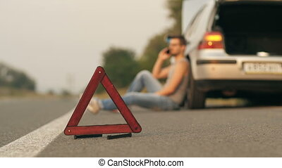 Young man sitting near broken car with cell phone - Road...
