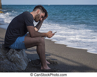 Young man sitting on a beach alone and lonely