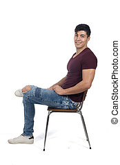 Young man sitting on a chair isolated on white