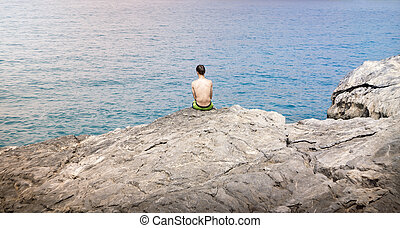 young man sitting on a cliff