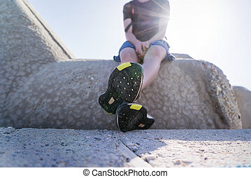 young man sitting on a concrete wall