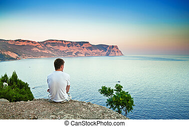 young man sitting on a hill and looking over the sea