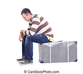 young man sitting on a luggage