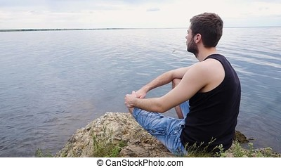 Young man sitting on a rock cliff above a rural lake....