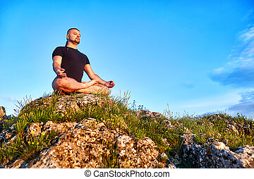 Young man sitting on a rock in the lotus position against blue sky with clouds.