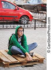Young man sitting on a sidewalk