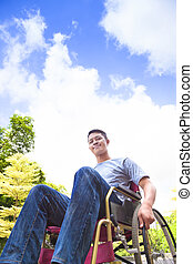 young man sitting on a wheelchair with natural background
