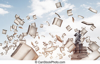 Young man sitting on books and do not want to see anything