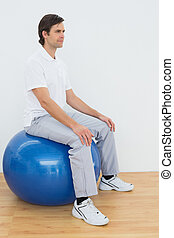 Young man sitting on exercise ball